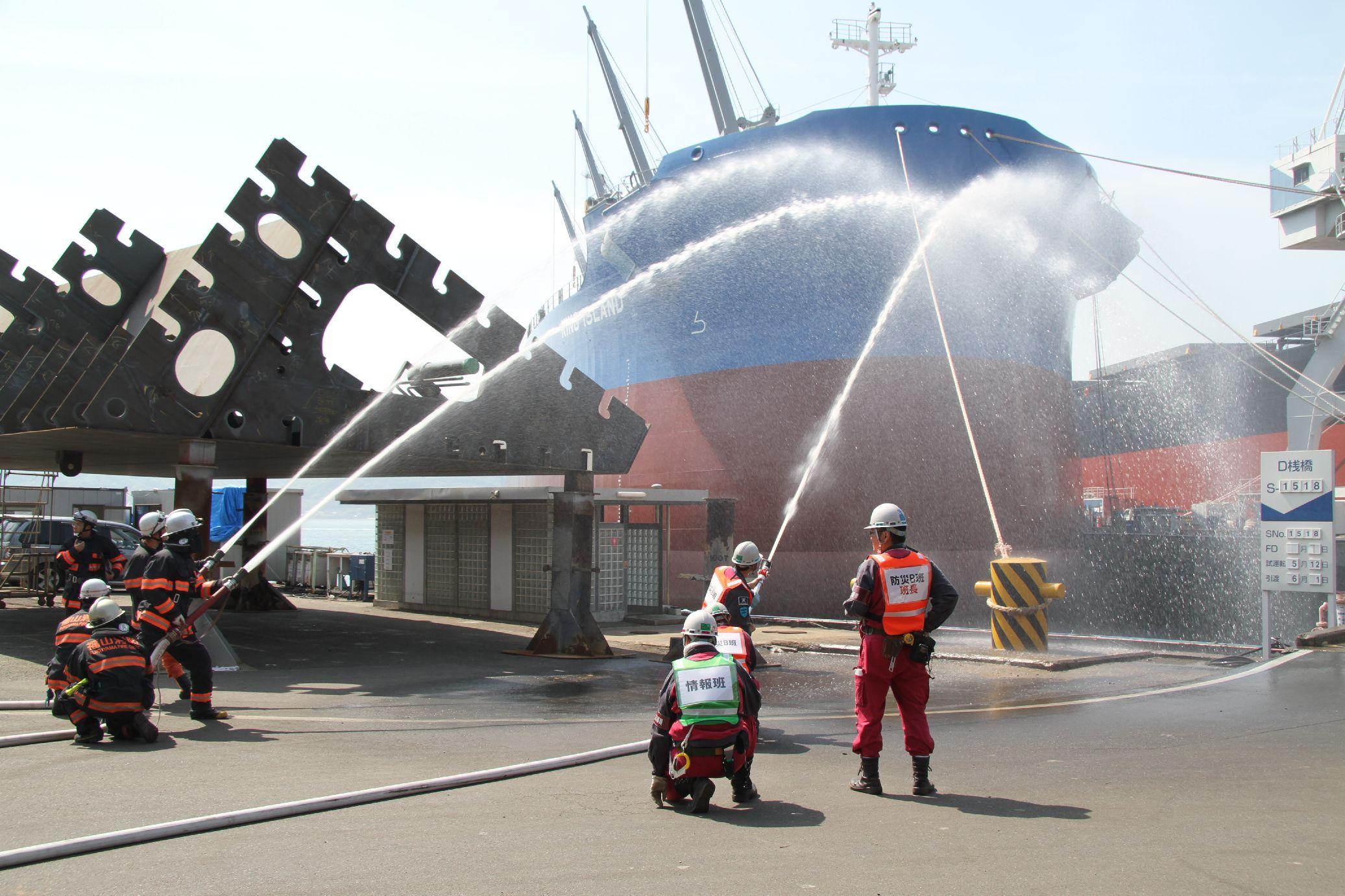 消防班が消防署職員と連携し、放水