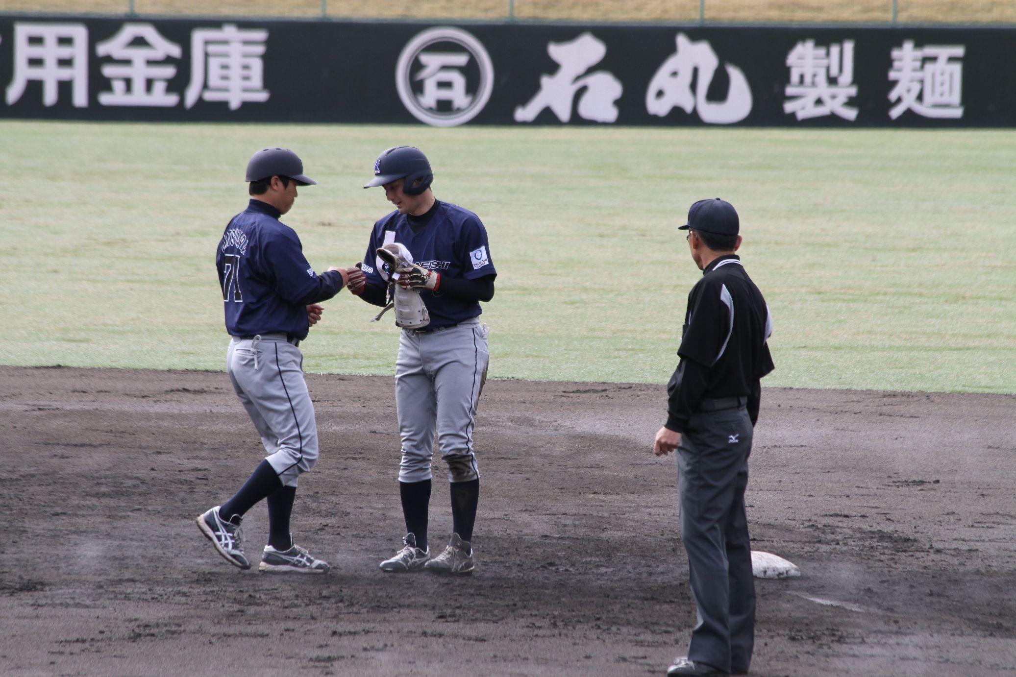 新人の斉藤選手の2塁打を称える松原勲コー チ