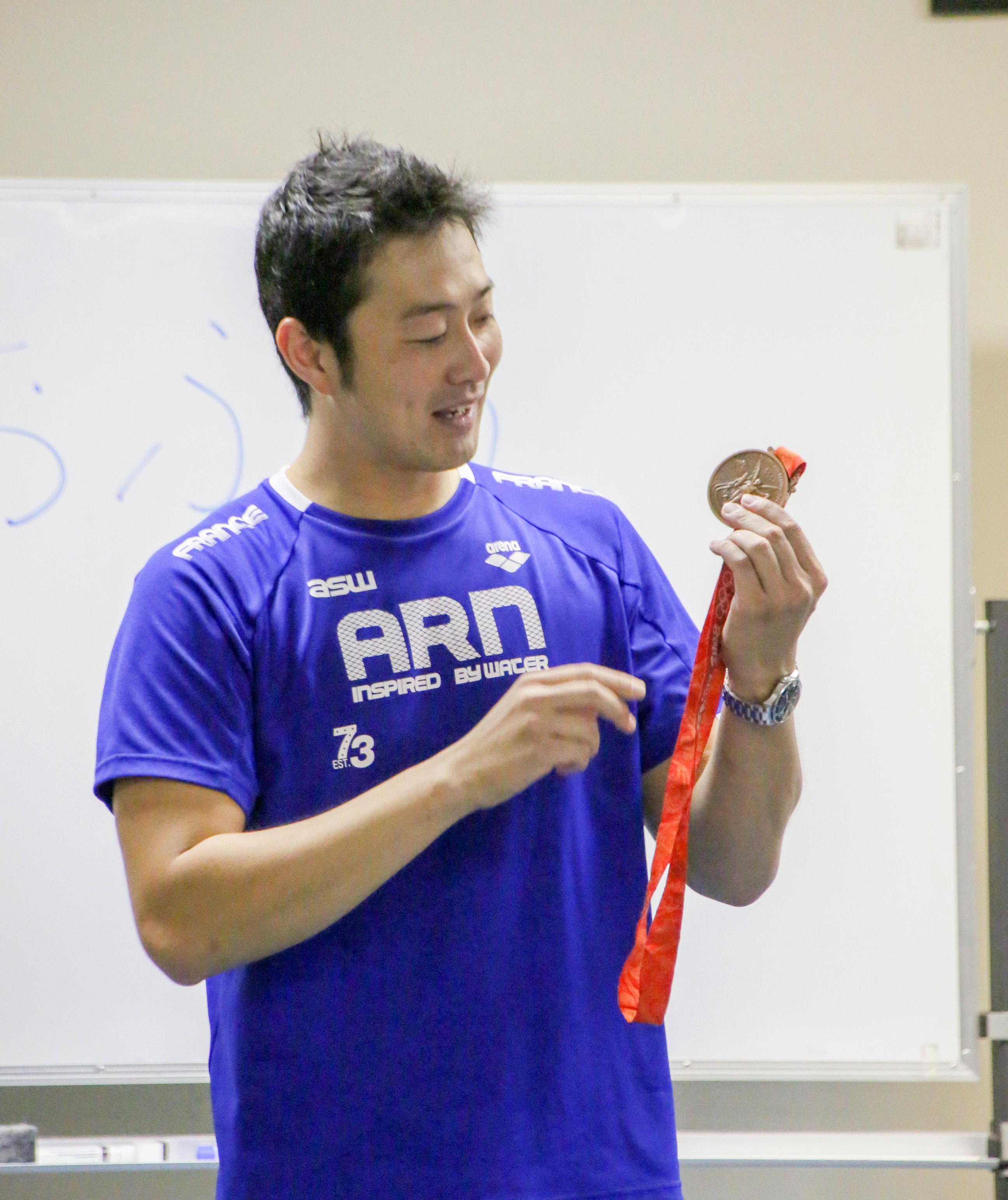 北京オリンピックの銅メダルを披露