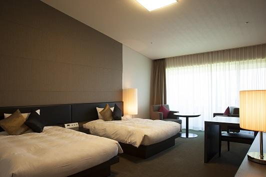落ち着いた配色の客室。シモンズ社の快適なベッド。
