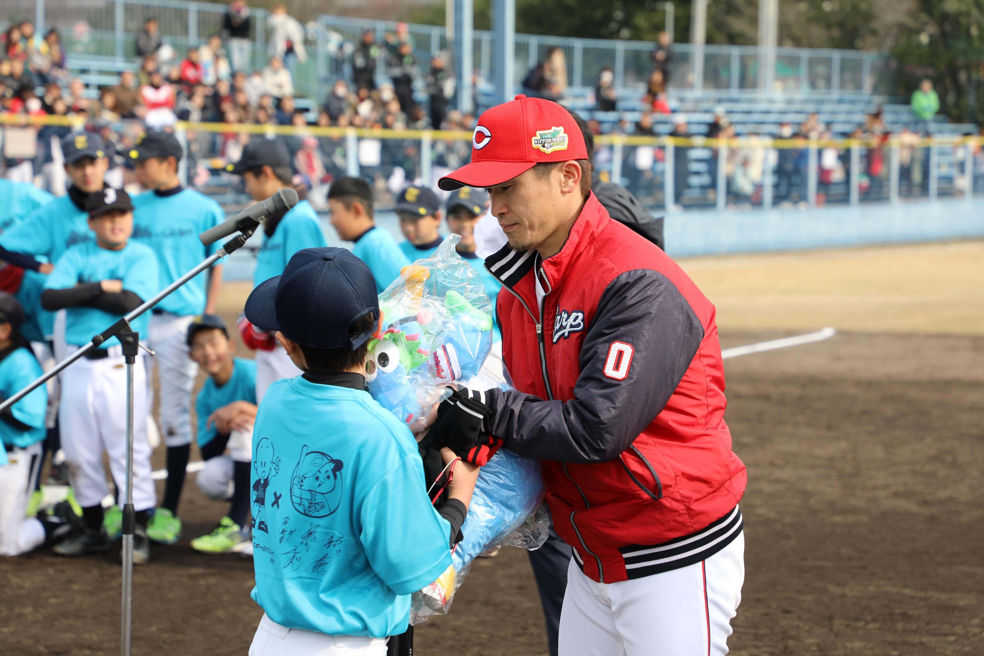 じゃんけんで勝ち残った参加者に広島東洋カープのマスコット・スラィリーを贈る上本選手